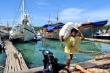 A young man unloading materials at the harbor.