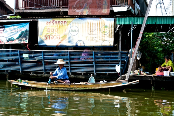 A man cooking next to the restaurant inside of the floating market.