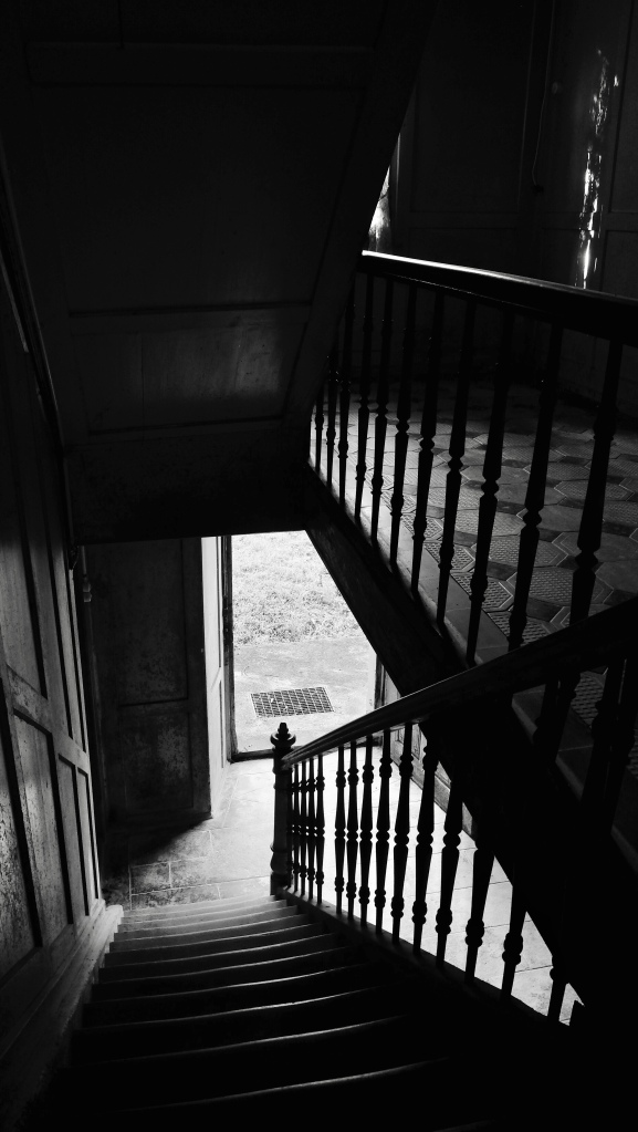 An eerie staircase leading up from the main door.